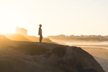 Woman in the top of a rock enjoying the beach view Imagens - 130027250