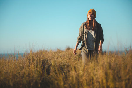 Beautiful woman with a yellow cap and walking over high grass