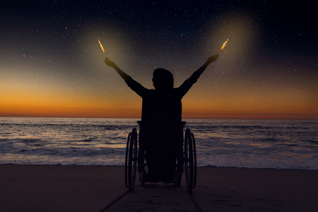 Handicapped woman in a wheelchair holding fire sparklers on a beautiful night Imagens