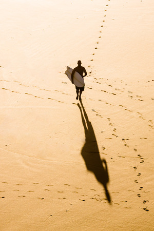 Top view of a surfer running on the beach Imagens - 130475608