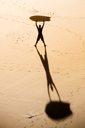 Top view of a surfer on the beach holding a surfboard Imagens - 130475580