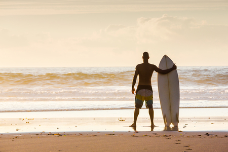 Surfer on the beach holding is surfboard and checking the waves Imagens