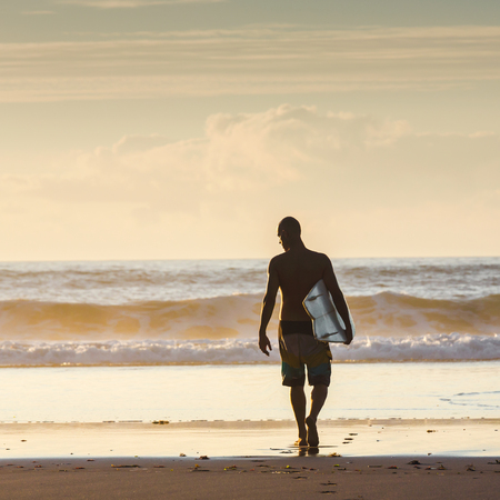 Surfer walking into the waves Imagens - 130475616
