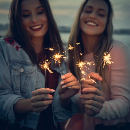 Two best friends celebrating, holding sparklers at beach Imagens - 130782910