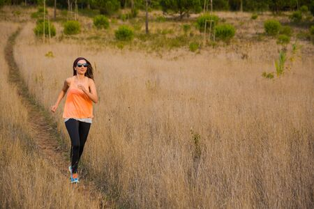 Shot of an attractive woman running outdoor on a meadow