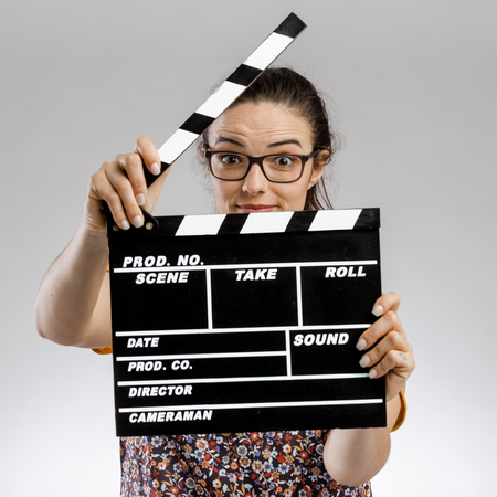 Portrait of a happy woman holding a clapboard