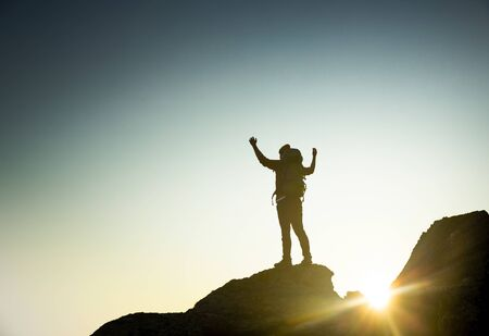 Shot of a man with arms raised and enjoying the of the montains at sunset