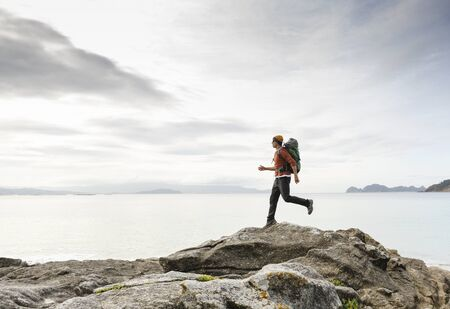 Man with backpack running over the rocks