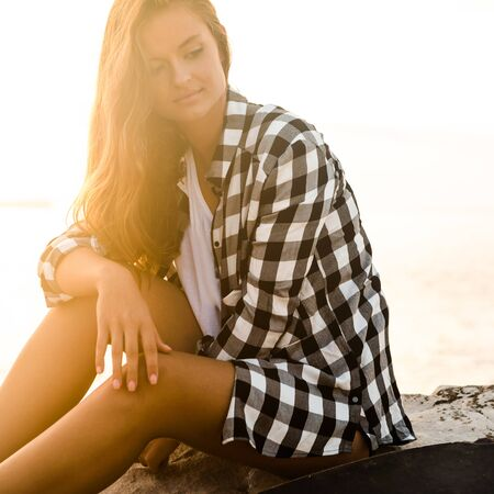 Beautiful young woman sitting on the rocks and relaxing at the sunset. Foto de archivo - 141063742