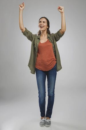 Beautiful and successful young woman with arms raised