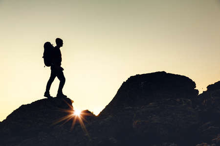 Shot of a man walking over the montains at sunset