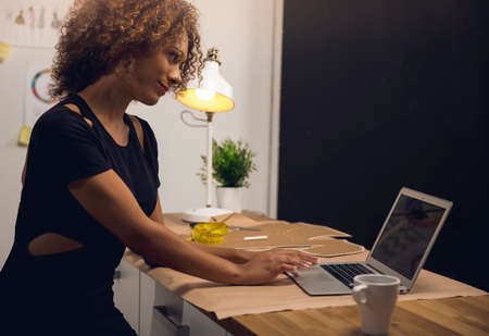 A young fashion designer on her atelier working with a laptop Фото со стока
