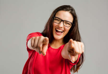 Happy woman smiling and pointing to the camera with both arms