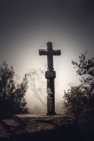 Shot of a beautiful religious stone cross on a foggy day