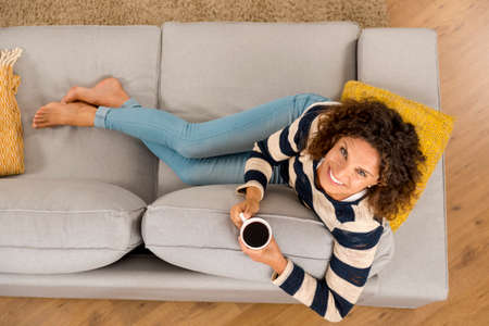 Top view of a beautiful woman on the sofa and drinking coffee