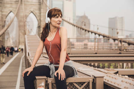 Woman sitting on the Brooklyn bridge and looking  the view Фото со стока