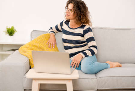 Beautiful woman at home sitting on the sofa and working with a laptop Фото со стока