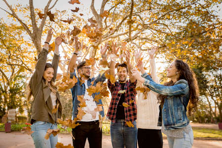 Group of friends in the park having fun throwing leaves in the air Фото со стока