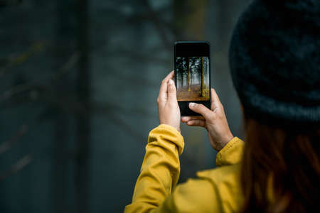 Female traveler taking a picture to a forest with her cellphone