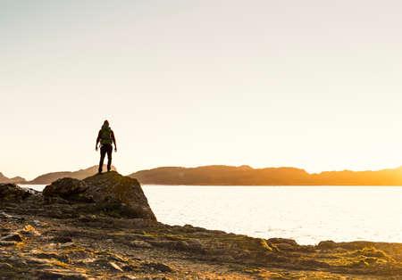 Shot of a man enjoying the view of the coast at sunset Фото со стока