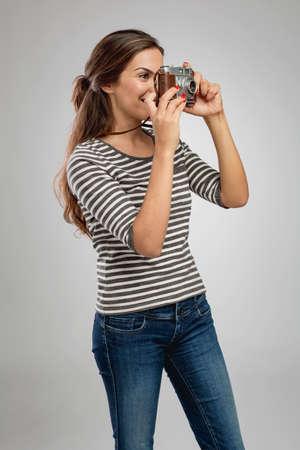 Portrait of a beautiful woman shooting with a vintage camera Фото со стока