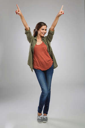 Beautiful and successful young woman with arms raised Фото со стока