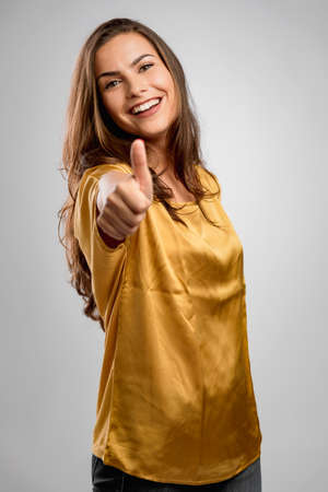 Beautiful young woman with a great smile with thumbs up Фото со стока