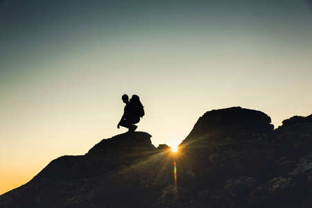 Shot of a man enjoying the view of the montains at sunset
