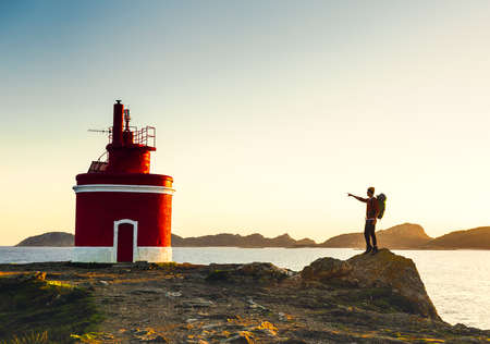 Man pointing to a beautiful ligthouse at sunset