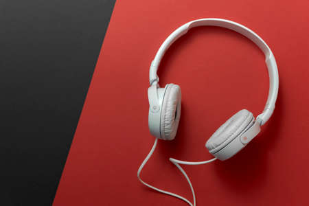 White headphones on a red-black background