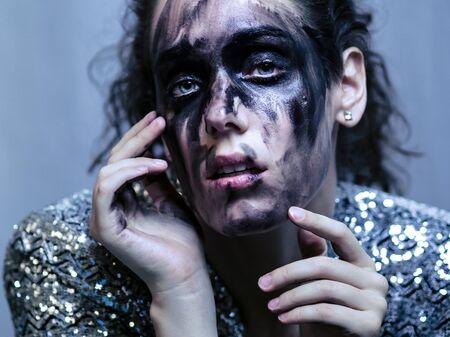 Alluring woman black painted face and glittery jacket