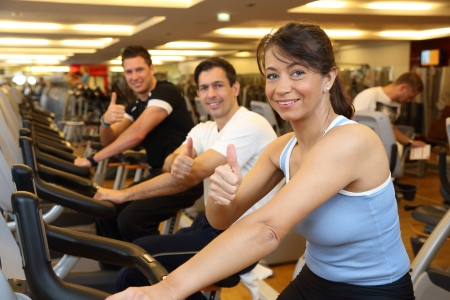 Group of people cycling in gym photo