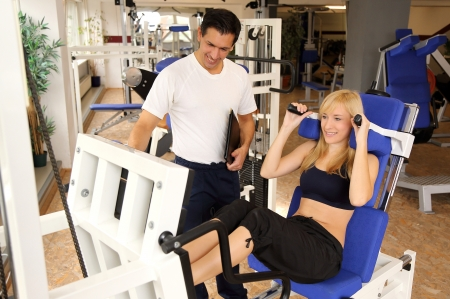 Personal trainer and athletic woman working out in a fitness center