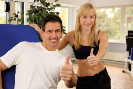 Personal trainer and athletic woman working out in a fitness center Stock Photo - 16715205