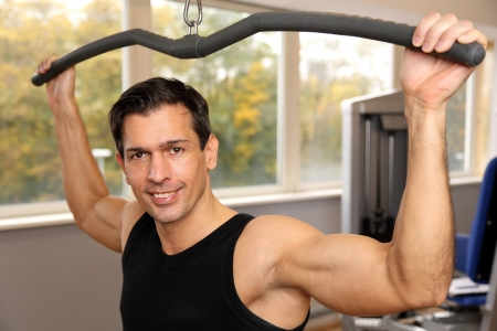 Athletic man exercising and lifting weights in a fitness center photo