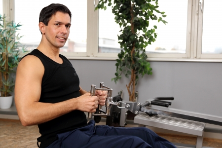 man working out: Athletic man exercising and lifting weights in a fitness center