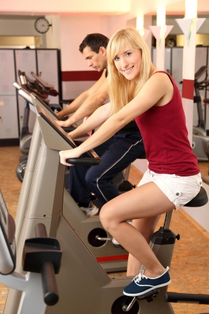 hometrainer: A handsome man and an attractive woman working out on a bicycle in a fitness center Stock Photo