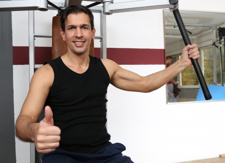 Athletic man exercising and lifting weights in a fitness center showing thumbs up photo