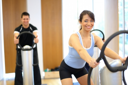Group of two men and one woman on a vibration massage plate in a gym photo