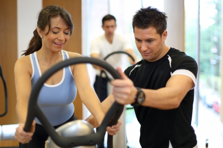 vibration: Instructor in a gym explains a vibration plate to a woman