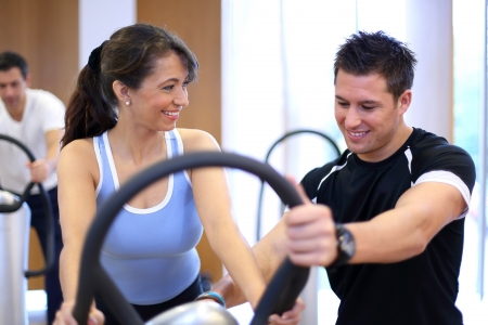 Instructor in a gym explains a vibration plate to a woman photo