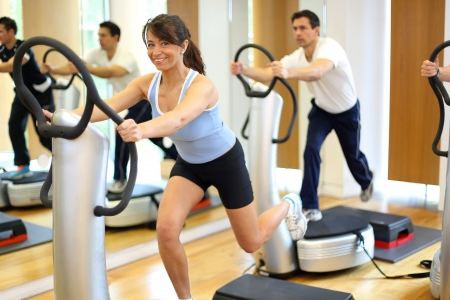 vibration machine: Group of two men and one woman on a vibration massage plate in a gym