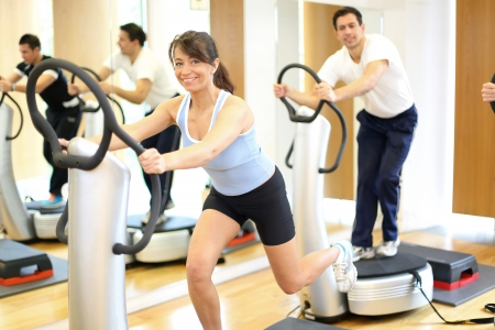 vibration: Group of two men and one woman on a vibration massage plate in a gym