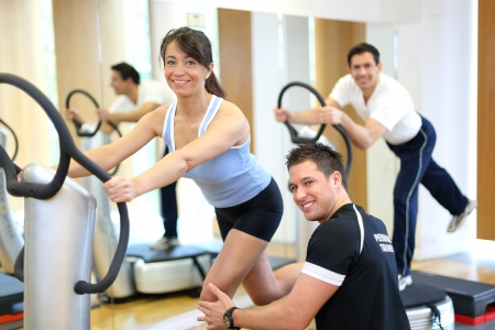 vibration: Woman on vibration plate in a gym instructed by personal trainer