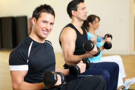 Two men and one woman exercising with dumbbells on gymnastics balls photo