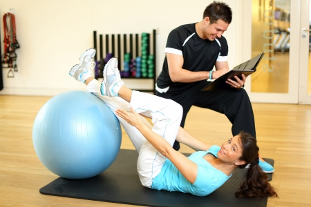 Instructor in a gym exercising with female customer