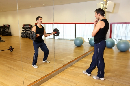 Athletic man watching his own reflection in the mirror lifting weights in a gym photo