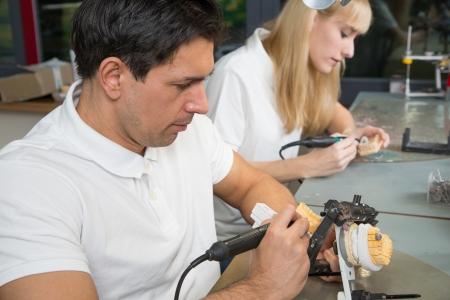 onlays: Técnico dental trabajando en una prótesis dental en un articulador