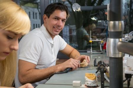 onlays: Dental Technicial con una pieza de mano en un laboratorio dental pulir el modelo de una prótesis. Foto de archivo