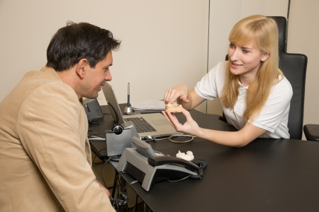 Dental technicial showing a model of a dental prosthesis to a customer or patient in her office photo